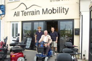 Ian and Liz with their dear friend Basil on his mobility scooter outside the front of the shop.