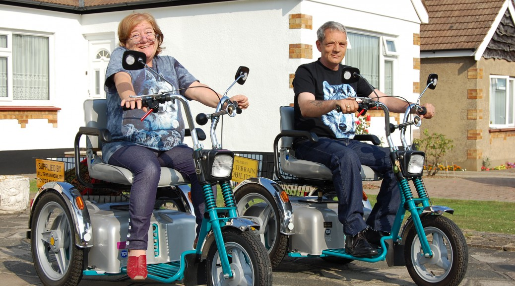 Rhona and Paul smiling sitting on their matching ' Harley Davidson style' three wheeled TGA super sport class 3 mobility scooters