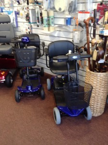 All Terrain Mobility Light Weight Travel Mobility Scooters pictured in blue but also available in red. These are small light weight scooters that are come apart for ease of transportation. Pictured here are the ATM Ultralight - mobility scooter and the ATM Aerolight mobility scooter.