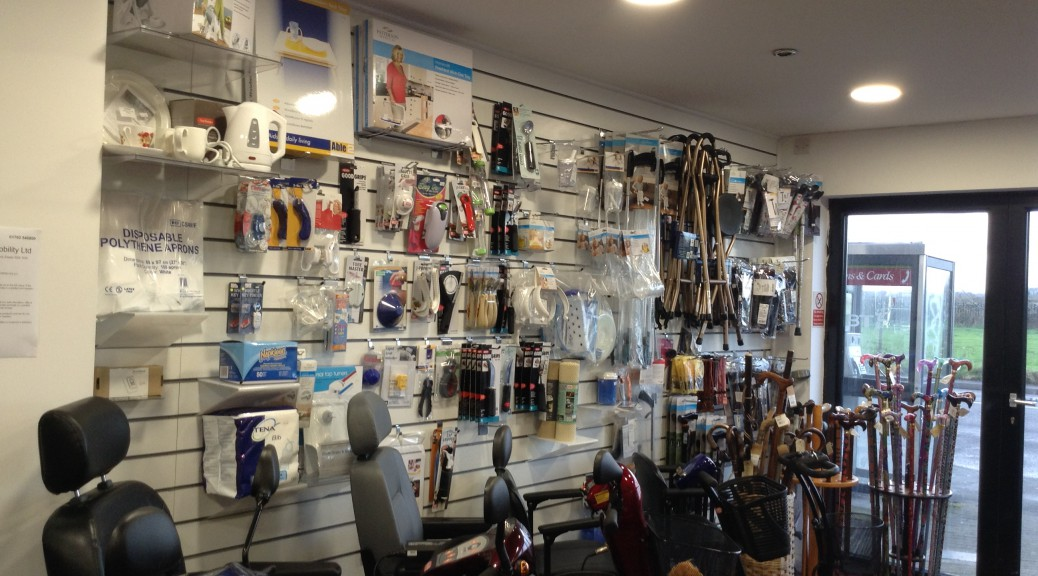 Here we have a picture of the inside of our mobility shop in Southend, Essex. Our walls are lined with a huge array of daily living aids. We have on show a small kettle, disposable polythene aprons, Tena disposable bibs, key safe, key turners, good grips cutlery, bottle openers, can openers, jar openers, stay tray with bean bag, 2 handled mug, two handled beaker, travel proof mug, reachers, grabbers, seat sticks, insulated mugs, stay warn bowels, walking sticks, mobility scooters, travel mobility scooters, kettle tipper