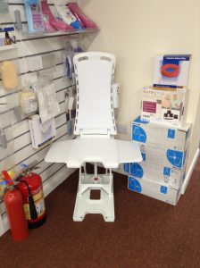 An All Terrain Mobility bath lift at All Terrain Mobility near Southend in Essex. With white covers also pictured are some of our bathroom aids such as long handled sponges, dry shampoo, inflatable wash basin, soapy soles, foot washer, sure grip chair raisers, inflatable rubber ring and elephant feet chair raisers
